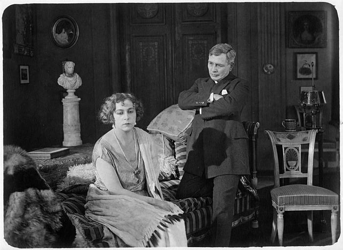 Nathalie Kovanko dans le rôle d'Hélène, assise sur un divan en compagnie d'un homme aux bras croisés dans 'Jean d'Agrève' de René Leprince