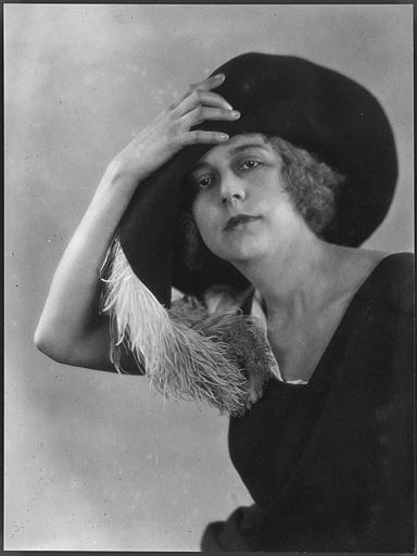 Portrait de Nathalie Kovanko tenant son chapeau garni d'une plume
