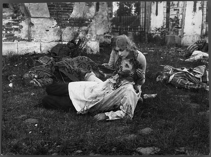 Une femme abreuvant un homme blessé au milieu d'un champs de bataille