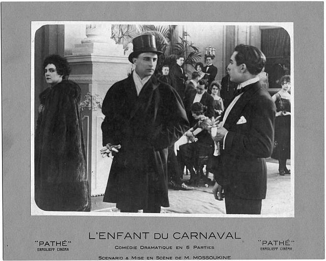 Nathalie Lissenko portant un manteau en fourrure, écoutant deux hommes qui discutent dans 'L'enfant du carnaval' de M. Mossoukine (Pathé)