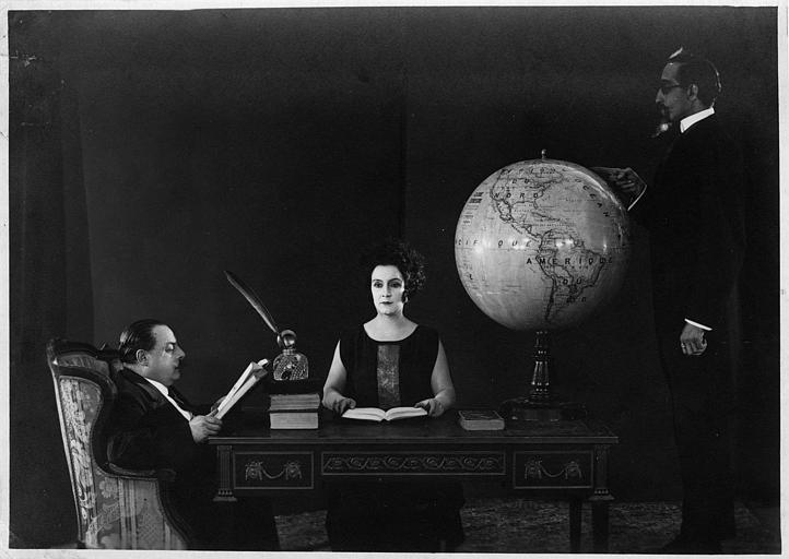 Nathalie Lissenko assise entre deux hommes à un bureau portant un globe terrestre
