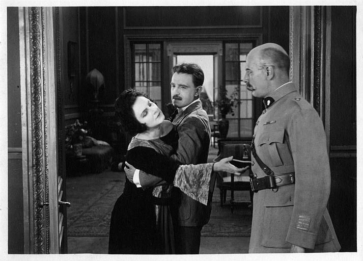 Nathalie Lissenko dans les bras d'un homme la retenant, tendant la main vers un officier