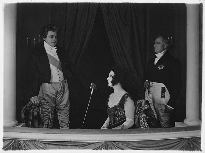 Nathalie Lissenko assise et deux hommes dans un balcon de théâtre