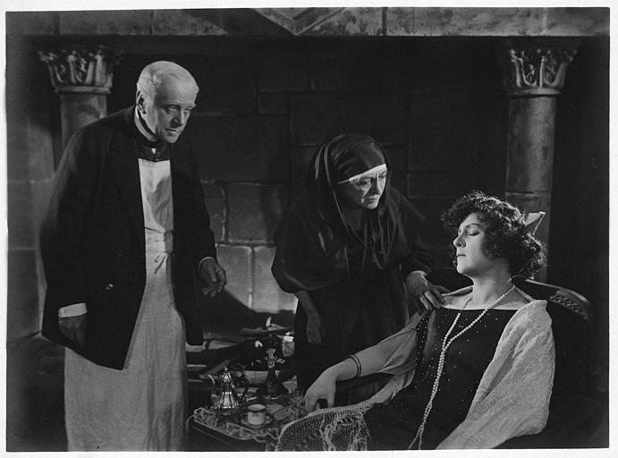 Nathalie Lissenko les yeux fermés dans un fauteuil avec un couple plus âgé devant une cheminée