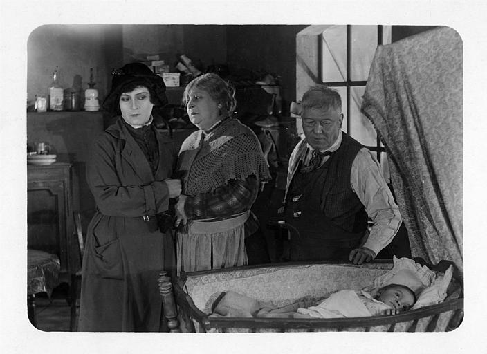 Nathalie Lissenko et deux personnages plus âgés devant un berceau