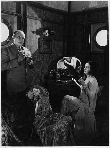 Nathalie Lissenko assise devant sa coiffeuse et un homme debout portant un monocle