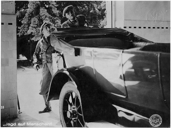 Deux hommes en bérets, dont Carlo Aldini, se cachant derrière une voiture dans 'Jagd auf Menschen' de Nunzio Malasomma (Internationaler Film Vertrieb)