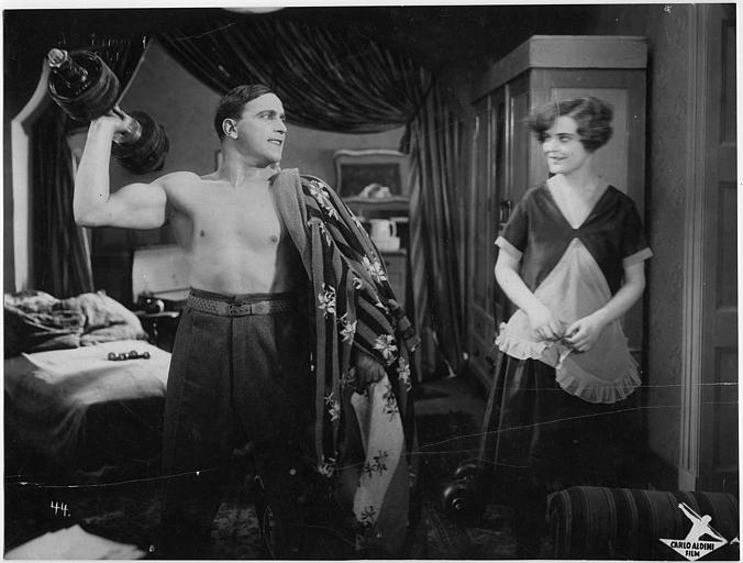 Carlo Aldini torse nu portant un haltère devant une jeune femme dans 'Jagd auf Menschen' de Nunzio Malasomma (Carlo Aldini film)