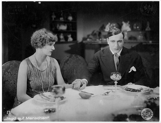 Carlo Aldini et une femme lui tenant la main à table dans 'Jagd auf Menschen' de Nunzio Malasomma