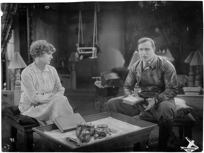 Carlo Aldini tenant un livre, et une femme, assis devant une table basse dans 'Jagd auf Menschen' de Nunzio Malasomma