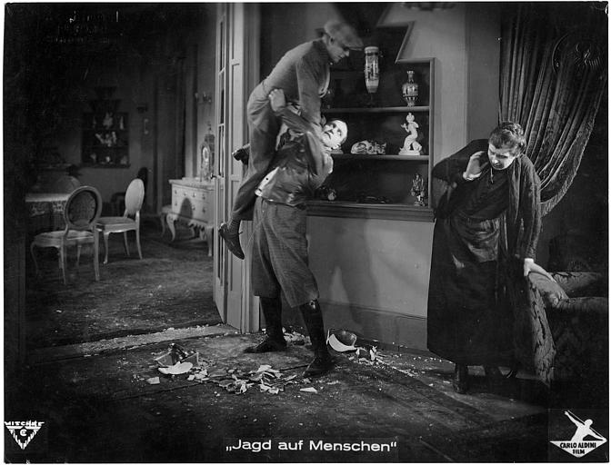 Carlo Aldini soulevant un homme face à une femme apeurée, vaisselle cassée au sol  dans 'Jagd auf Menschen' de Nunzio Malasomma