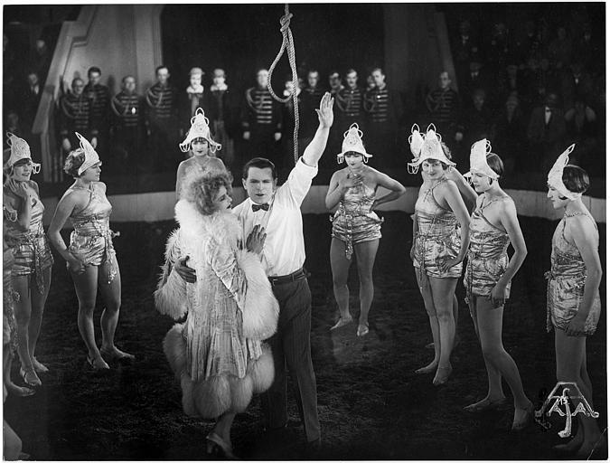 Luciano Albertini jouant Silvio Spaventa au milieu d'une piste de cirque, entouré de plusieurs femmes dans 'Der Unüberwindliche' (AFA)