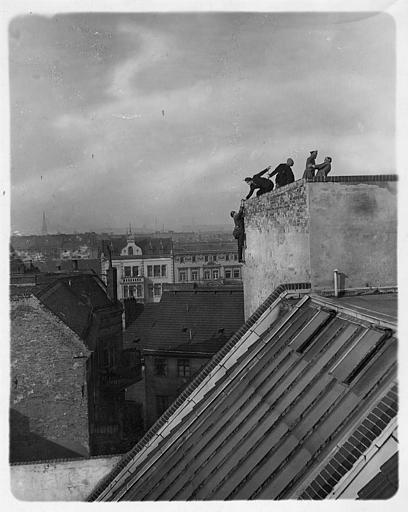 Cinq personnages dont Harry Piel sur le toit d'un immeuble duquel on voit toute la ville, dans 'L'aventure d'une nuit' d'Harry Piel