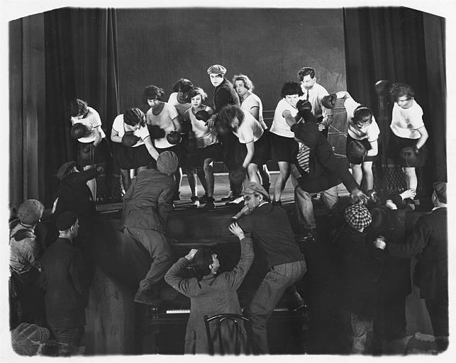 Des jeunes femmes en gants de boxe, sur une scène, se battant avec des spectateurs : Harry Piel dans 'L'aventure d'une nuit' d'Harry Piel