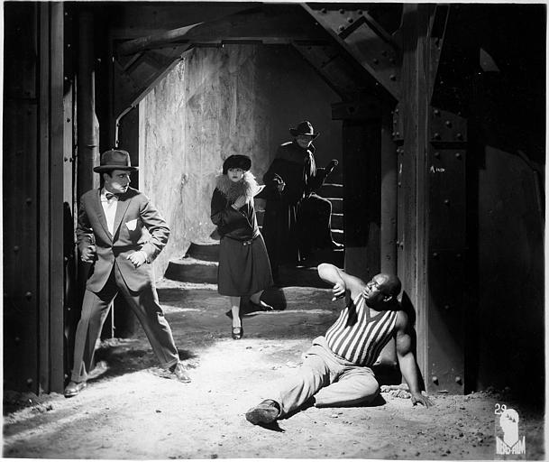 Quatre personnages dont Harry Piel : un homme et une femme fuyant dans un escalier tandis qu'un troisième homme est au sol et qu'un quatrième menace de le frapper