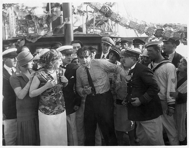 Sur le pont d'un bateau, foule autour d'Harry Piel trempé (jouant un personnage qui porte son propre nom) dans 'Face à la mort' d'Harry Piel et Gérard Bourgeois