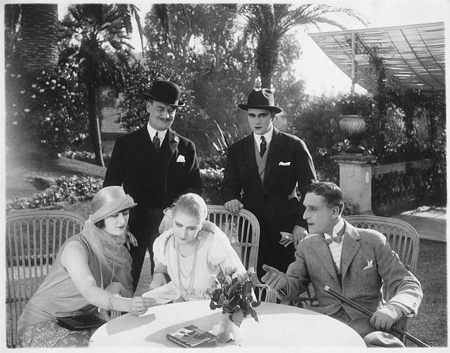 Deux femmes regardant des images assises à côté d'un homme tandis qu'Harry Piel et un troisième homme, debout derrière, les observent  dans 'Face à la mort' d'Harry Piel et Gérard Bourgeois