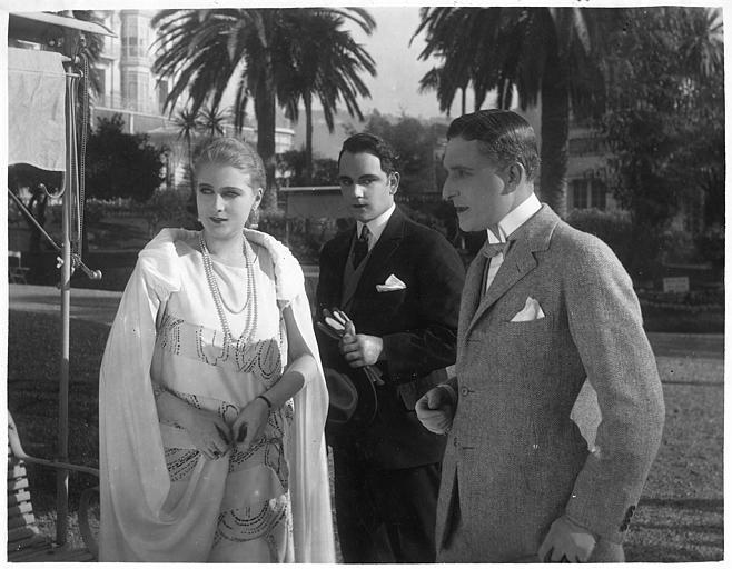 Une femme discutant avec Harry Piel et un autre homme, palmiers à l'arrière plan, dans 'Face à la mort' d'Harry Piel et Gérard Bourgeois
