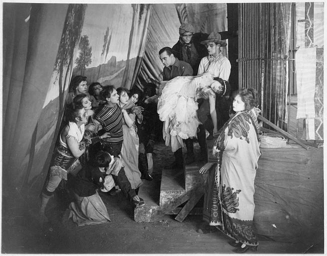 Loïs Moran portée par Jean Murat et le dompteur Rosar montant un escalier sous le regard d'un groupe de personnages entourant Jacques Catelain dans 'La galerie des monstres' de Jacques Catelain (FI Cinegraphic)