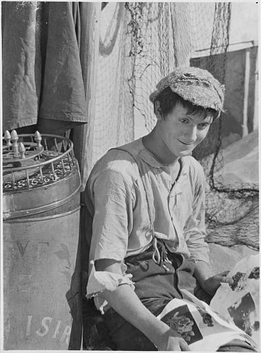 Jaques Catelain assis, appuyé sur un tonneau, portant des vêtements déchirés dans 'Le marchand de plaisirs' de Jaques Catelain (FI Cinegraphic)