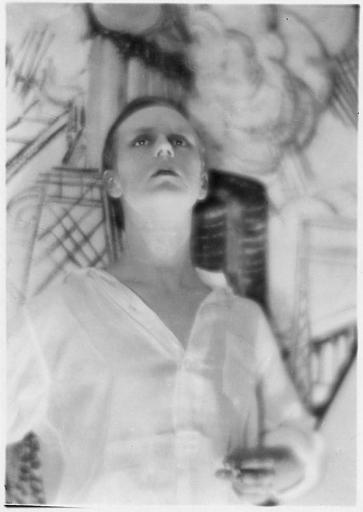 Portrait de Jaques Catelain dans le flou, devant un décor dessiné, une cigarette à la main