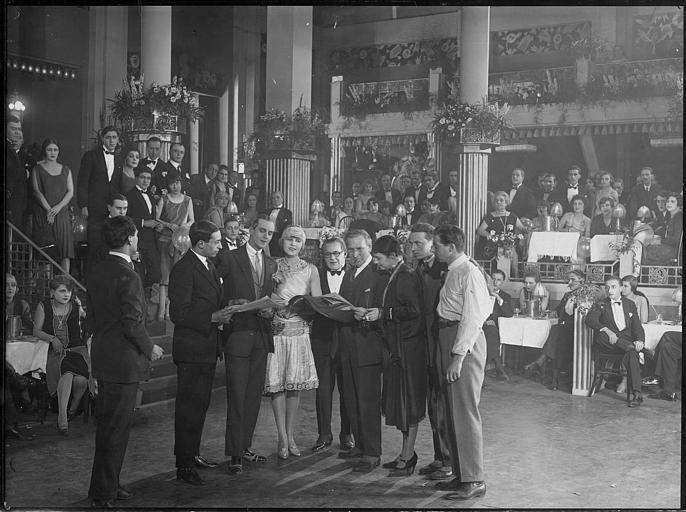 Jaques Catelain interprète Mylord et Lia Eibenschuntz interprète Winnie, tous deux entourés d'autres personnages dont certains lisent des journaux au milieu d'une salle de music-hall