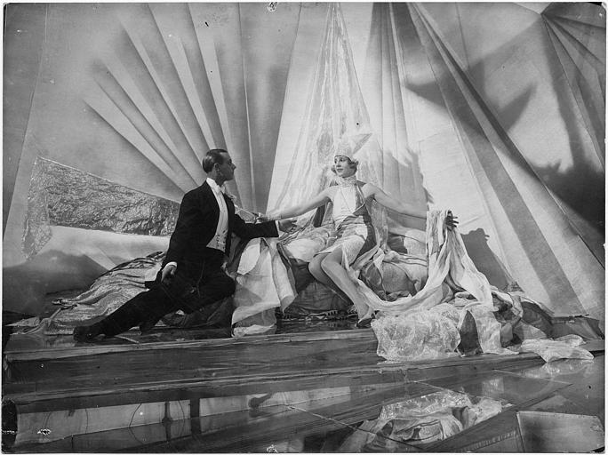 Sur une scène de spectacle, Lia Eibenschuntz assise sur un lit accueille un homme les bras ouverts