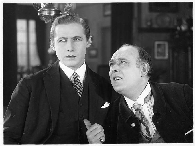 Jean Dehelly dans le rôle d'Albert Delpierre discute avec M. Beulemans interprété par Gustave Libeau dans 'Le mariage de Mademoiselle Beulemans' de Julien Duvivier