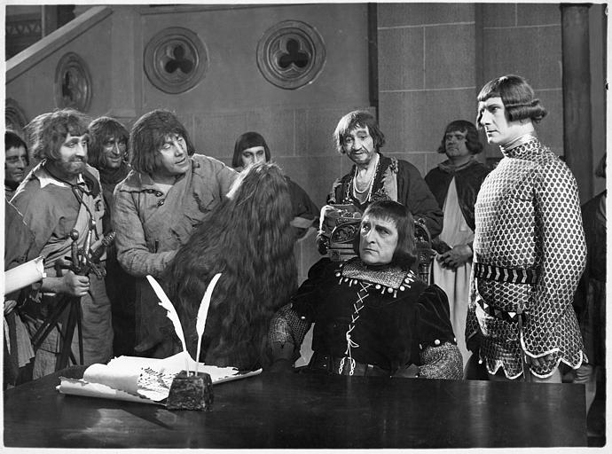 Des paysans présentant à un seigneur assis à table la chevelure d'une femme : Georges Melchior joue Loys Millet et Maxime Desjardins joue Etienne Marcel dans 'Florine, la fleur du Valois' de Donatien
