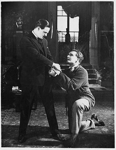 Malcolm Todd dans le rôle d'André ou de Justin Cornélis se jetant aux pieds de Georges Lannes interprétant Jacques Termonde dans 'André Cornélis' de Jean Kemm