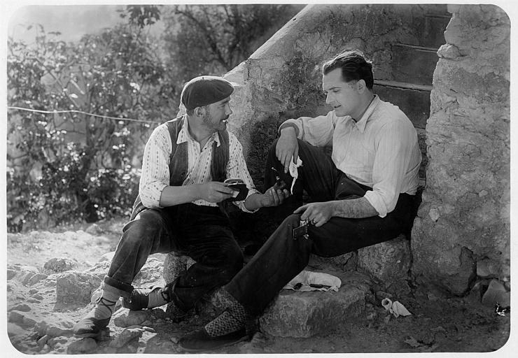 Georges Lannes dans le rôle de Jacques Termonde assis, discutant avec un autre homme en bas des marches d'un escalier en pierre