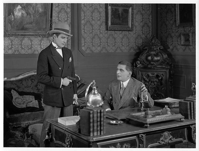 Un homme menaçant d'un revolver un autre homme assis à son bureau : Léon Bary est Jean le Morel et Acho Chakatouny est Paul Gaine dans 'La menace' de Jean Bertin