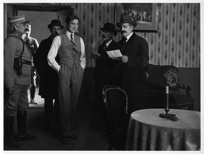 Un homme fumant une cigarette entrant dans une pièce accompagné de cinq hommes : Léon Bary est Jean le Morel dans 'La menace' de Jean Bertin
