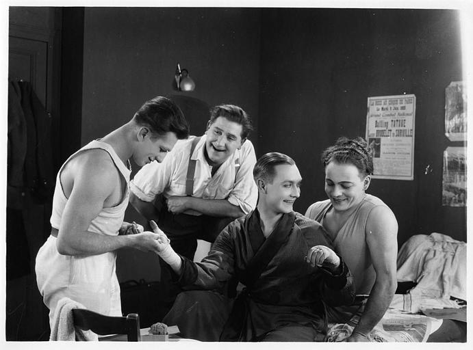 Deux hommes et Olga Day entourant André Roanne qui a les mains bandées dans 'Chouchou poids plume' de Gaston Ravel