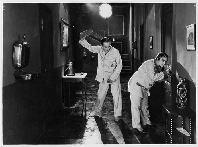 Un homme s'apprête à taper avec son chausson les fesses d'une femme écoutant à une porte