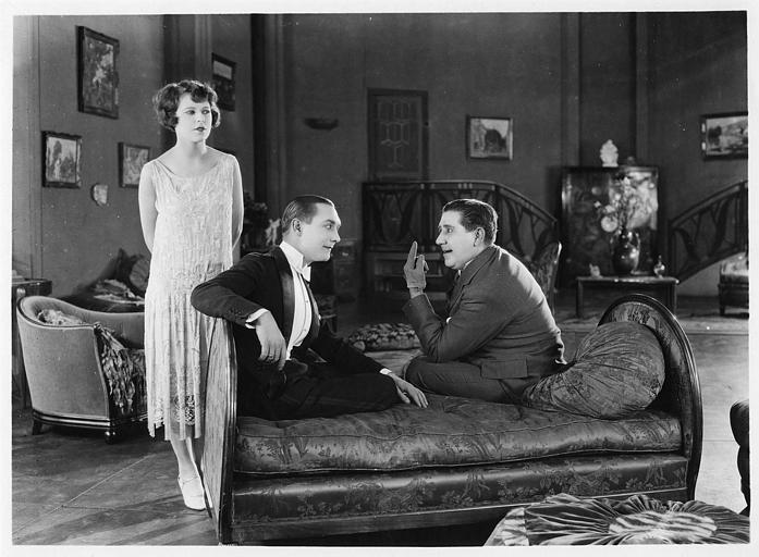 Deux hommes assis sur un sofa dicutant et une femme en robe blanche se tenant debout