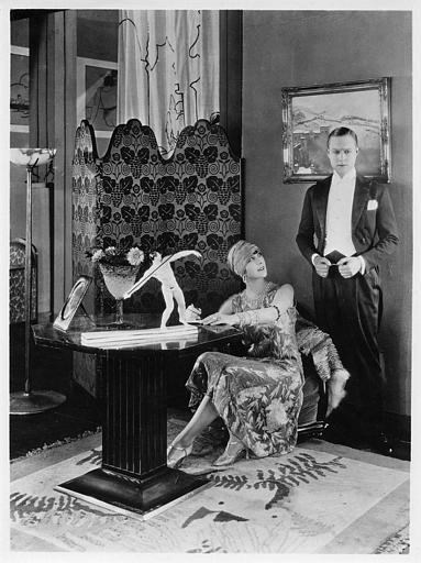 Une femme assise à un bureau devant la statuette d'un lanceur de javelot, regardant un homme en smoking debout derrière elle