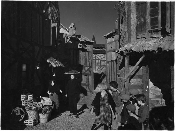 Dans la rue d'un village, un homme porte un plateau sur sa tête tandis qu'il est entouré d'enfants et de deux femmes