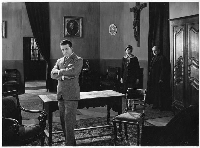 Aimé Simon-Girard, dans le rôle de Jacques de la Ferlandière, se croisant les bras et derrière lui, Maria Dalbaicin et un prêtre dans 'La grande amie' de Max de Rieux