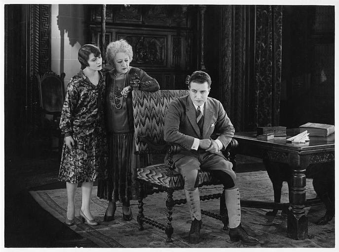 Aimé Simon-Girard, dans le rôle de Jacques de la Ferlandière, assis sur une chaise avec deux femmes dans son dos dans 'La grande amie' de Max de Rieux
