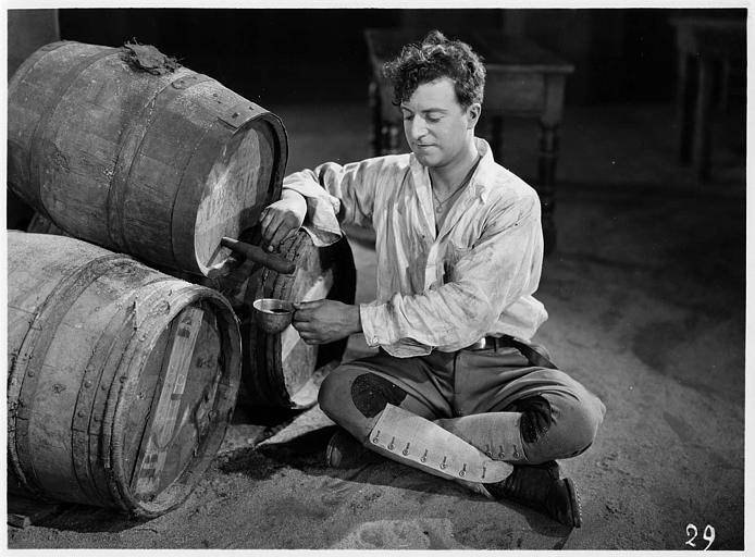 Aimé Simon-Girard, dans le rôle de Jacques de la Ferlandière, assis au sol et se servant une tasse de vin au tonneau dans 'La grande amie' de Max de Rieux