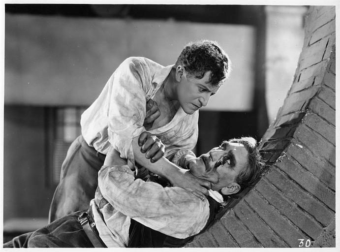 Aimé Simon-Girard, dans le rôle de Jacques de la Ferlandière, étranglant un homme à la joue ensanglantée dans 'La grande amie' de Max de Rieux