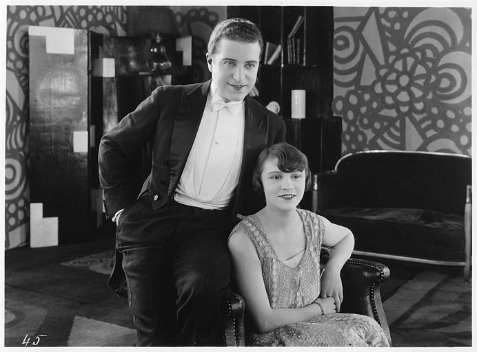 Aimé Simon-Girard, dans le rôle de Jacques de la Ferlandière, s'appuyant sur l'accoudoir d'un fauteuil où est assise une jeune femme dans 'La grande amie'  de Max de Rieux
