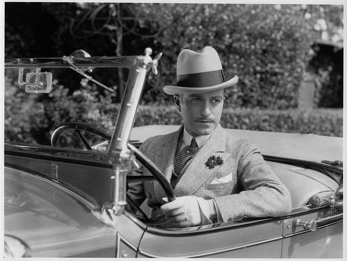 Un homme portant un chapeau au volant d'une voiture