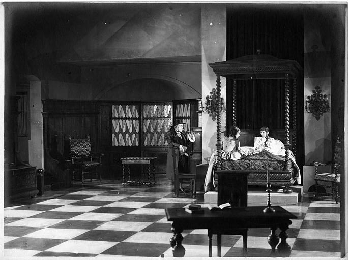 Dans une chambre à coucher, trois personnages en costume, dont deux jeunes filles sur le lit