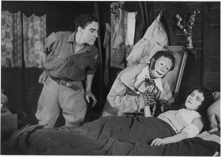 Une jeune femme alitée visitée par un clown et un homme se penchant vers le lit