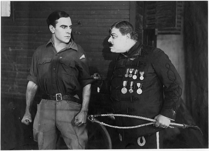 Un homme portant des médailles et un fouet en menaçant un autre, portant une chemise déchirée