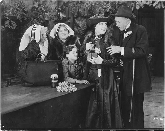 Deux femmes portant une coiffe, un enfant, un vieillard et une femme discutant autour d'une table : Géraldine Farrar est Marcia Manot et Tully Marschall est Silas Martin dans 'The Devil Stone' de Cecil B. DeMille