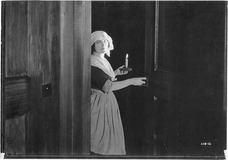 Géraldine Farrar, dans le rôle de Marcia Manot, porte un bougeoir et ouvre une porte dans 'The Devil Stone' de Cecil B. DeMille