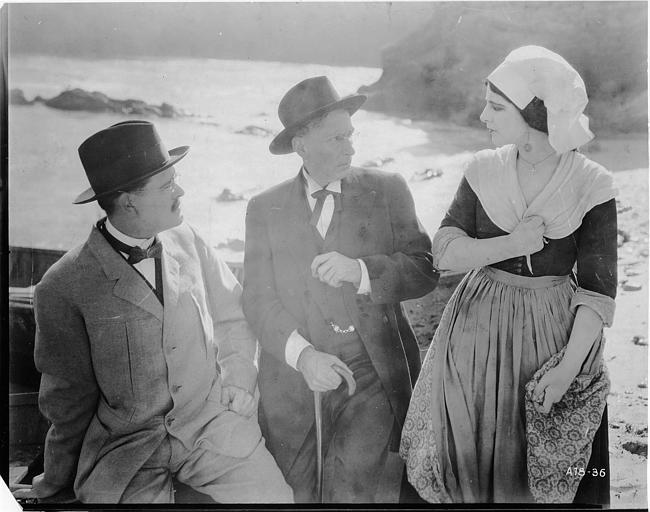 Géraldine Farrar, dans le rôle de Marcia Manot, avec deux hommse au bord de la mer dans 'The Devil Stone' de Cecil B. DeMille